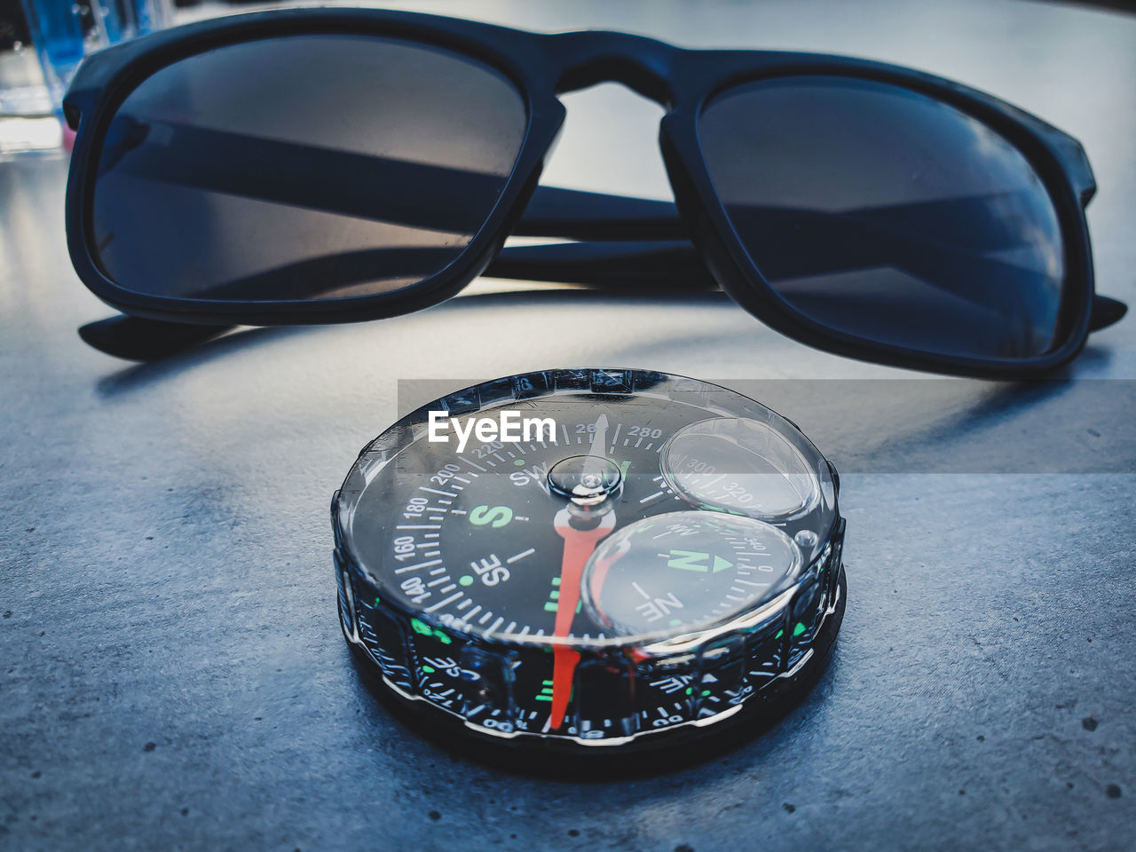 CLOSE-UP OF SUNGLASSES WITH REFLECTION ON GLASS