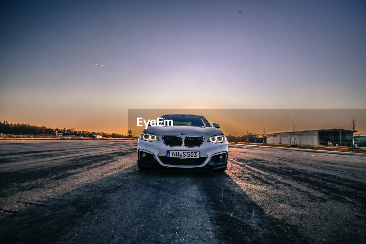 sunset, transportation, car, road, sky, outdoors, land vehicle, clear sky, no people, nature, day, city, close-up