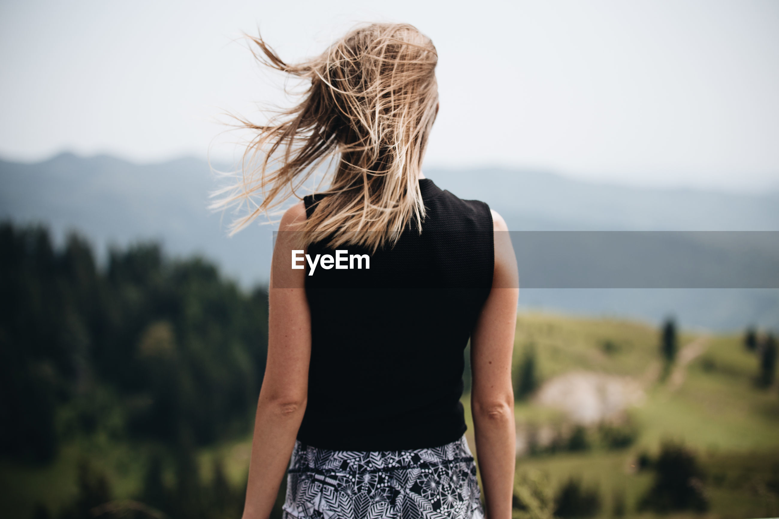 Rear view of woman with tousled blond hair standing against mountains