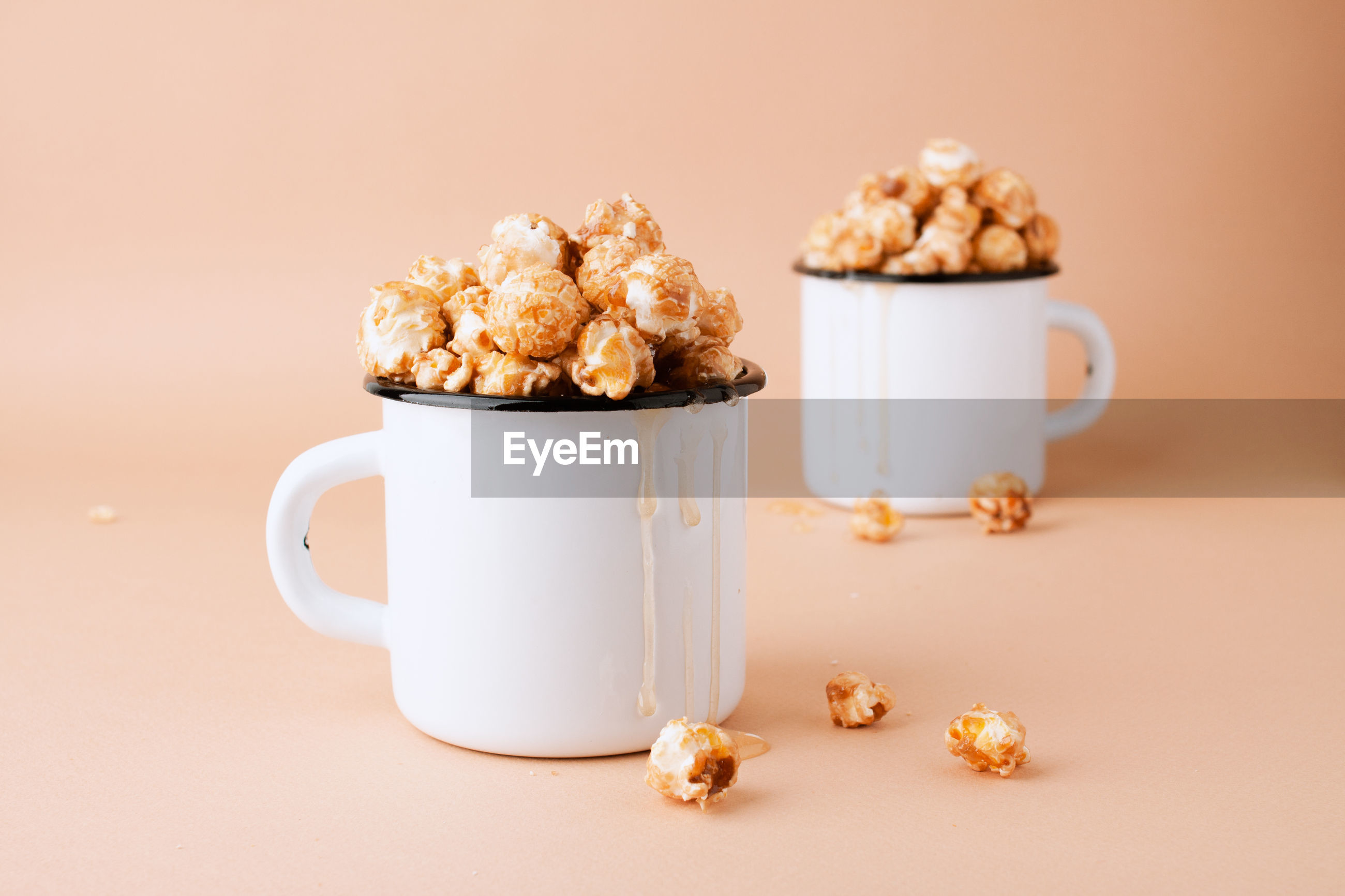 Caramel popcorn in vintage white metal cups on a brown background