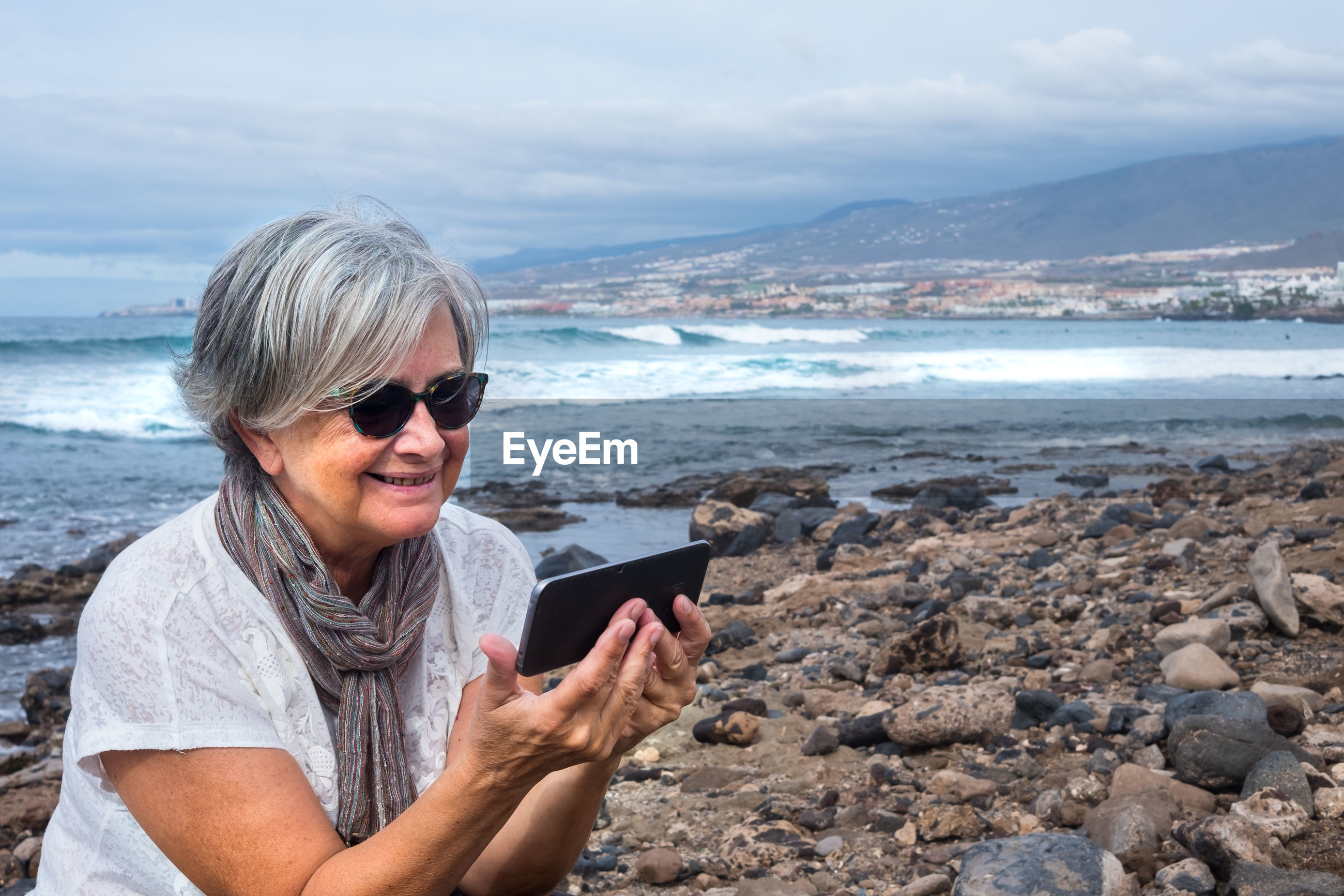 Smiling senior woman using mobile phone while sitting at beach against sky