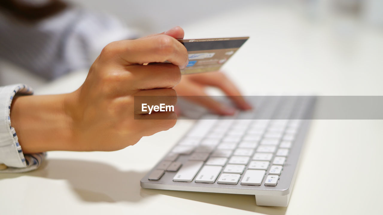 Cropped Hand Using Credit Card While Working At Desk