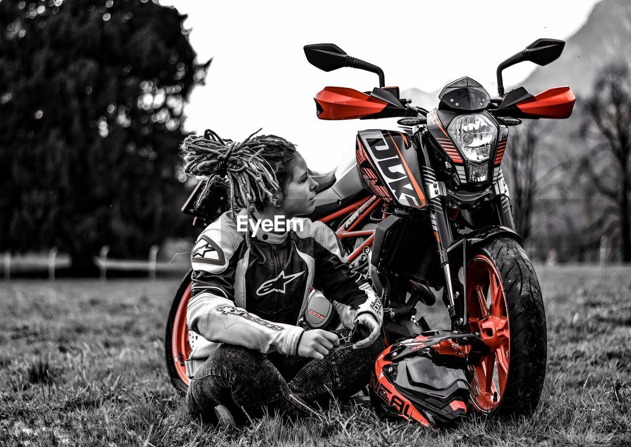 motorcycle, transportation, riding, mode of transport, field, land vehicle, sports clothing, real people, two people, outdoors, motorcycle racing, lifestyles, grass, sitting, day, motocross, biker, tree, nature, sky, people