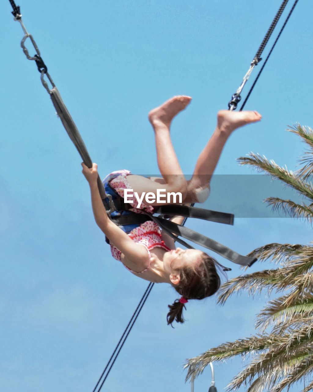 real people, clear sky, low angle view, leisure activity, one person, upside down, full length, day, outdoors, risk, mid-air, lifestyles, skill, sky, acrobat, tree, extreme sports, rope swing, acrobatic activity, nature, beauty in nature, young adult, people