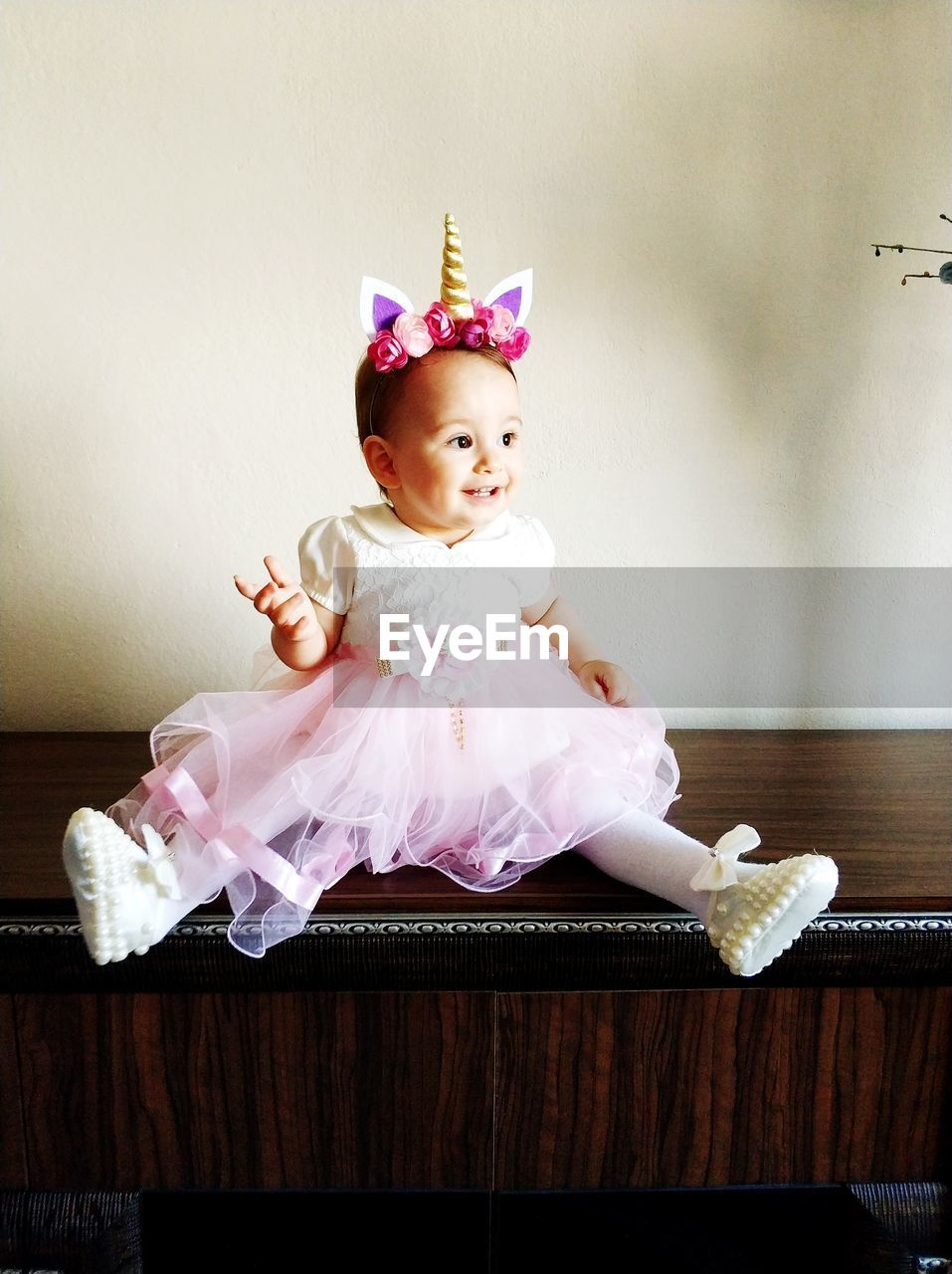 Full Length Of Cute Smiling Baby Girl Sitting On Cabinet At Home