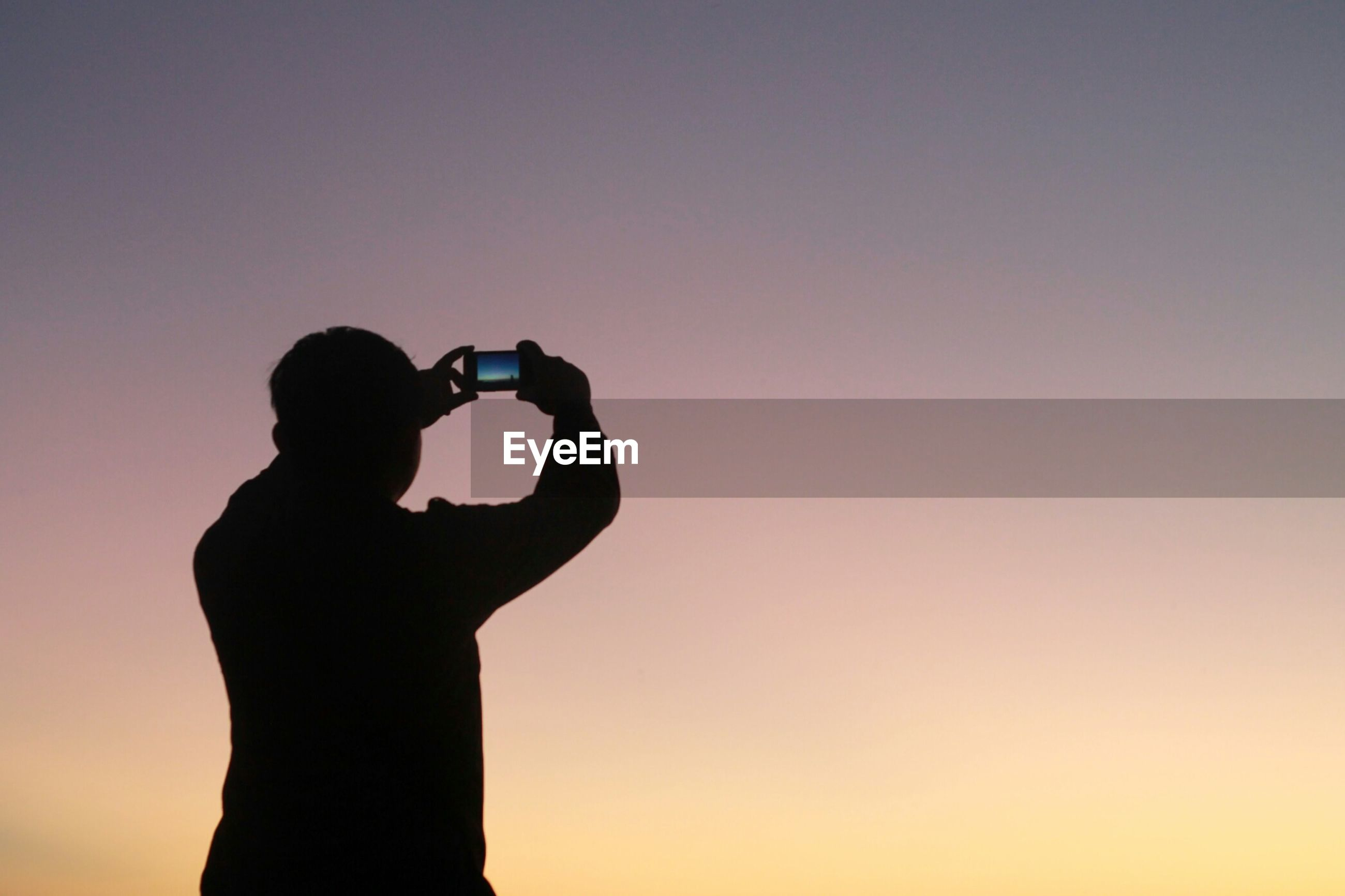 Silhouette man photographing clear sky at dusk