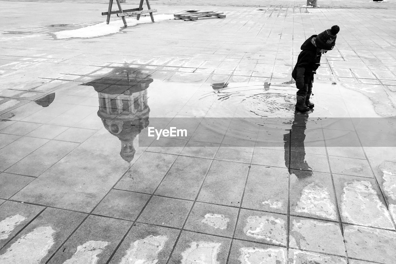 Boy standing on puddle with reflection of building on pavement