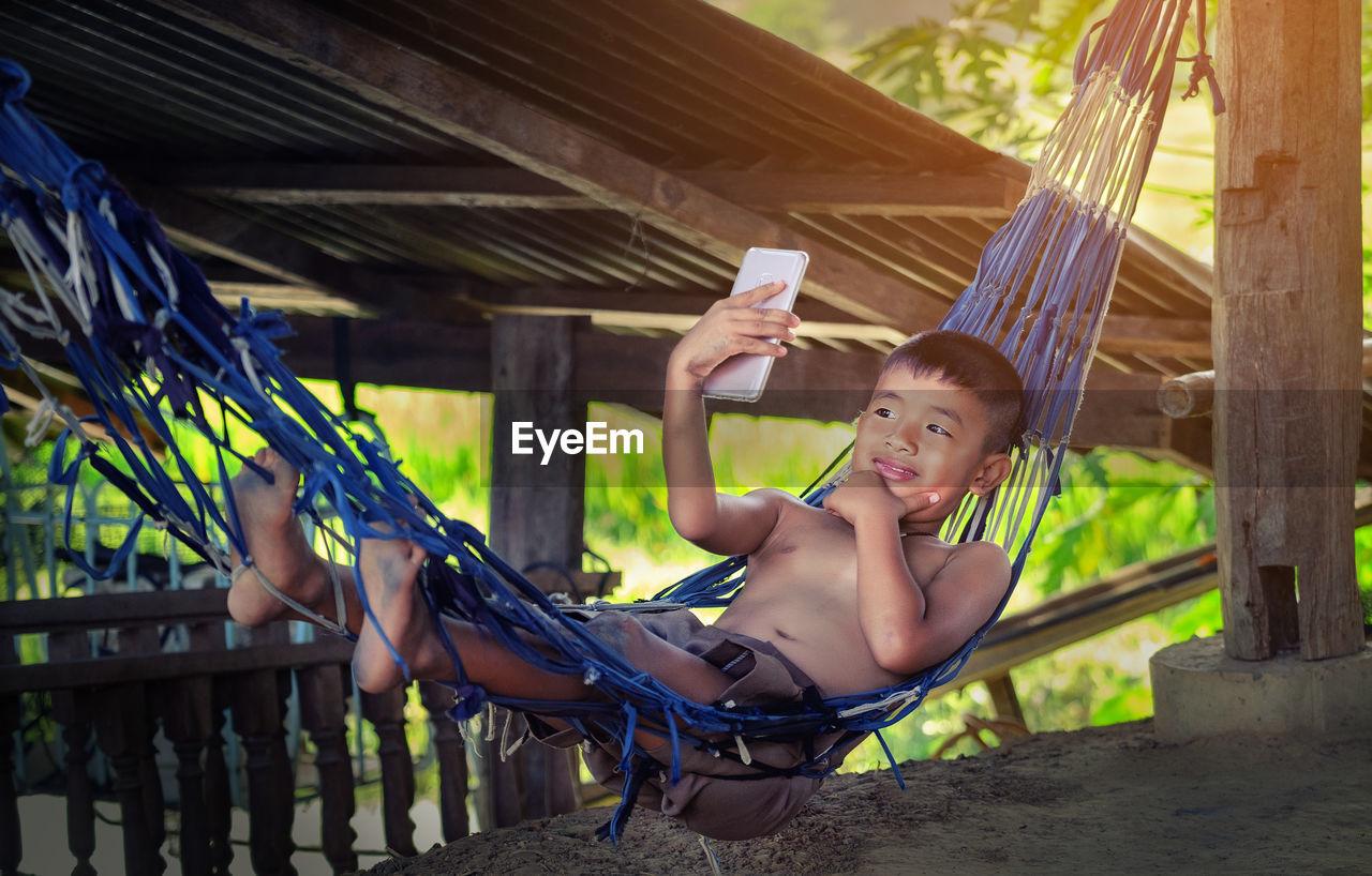 Cute Boy Lying On Hammock Taking Selfie From Smart Phone