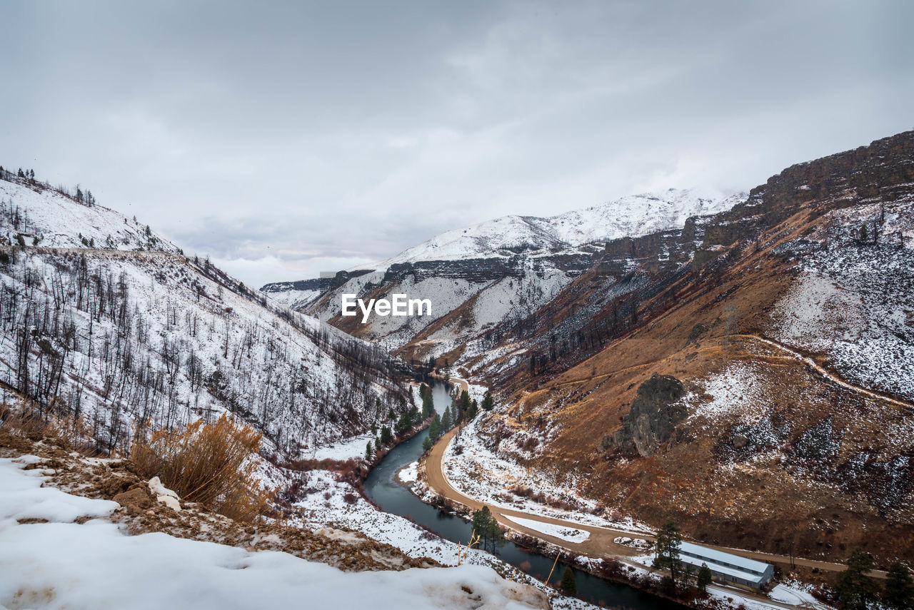 Aerial view of river flowing amidst snowcapped mountains