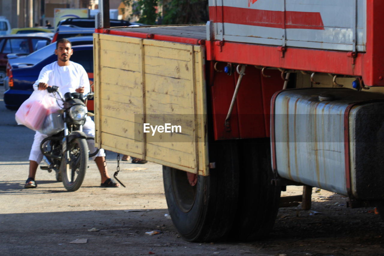 transportation, real people, land vehicle, mode of transport, one person, outdoors, men, day, full length, casual clothing, bicycle, riding, lifestyles, occupation, motorcycle, helmet, mammal