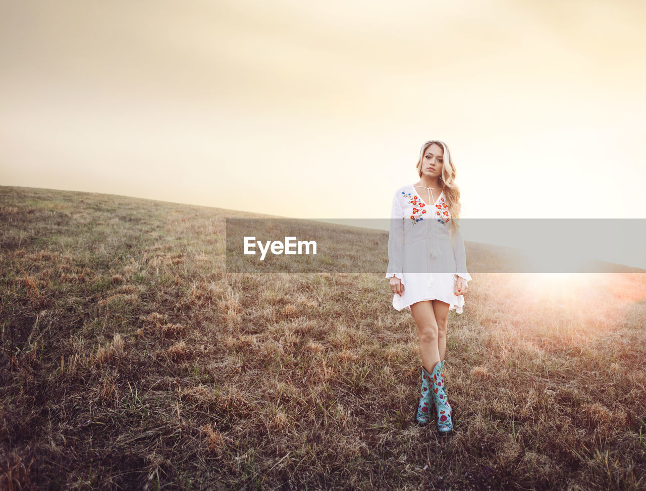 one person, front view, full length, real people, standing, nature, grass, outdoors, lifestyles, sunset, young adult, leisure activity, walking, casual clothing, field, looking at camera, sunlight, beautiful woman, portrait, landscape, young women, happiness, day, sky, clear sky, beauty in nature, blond hair, adult, people