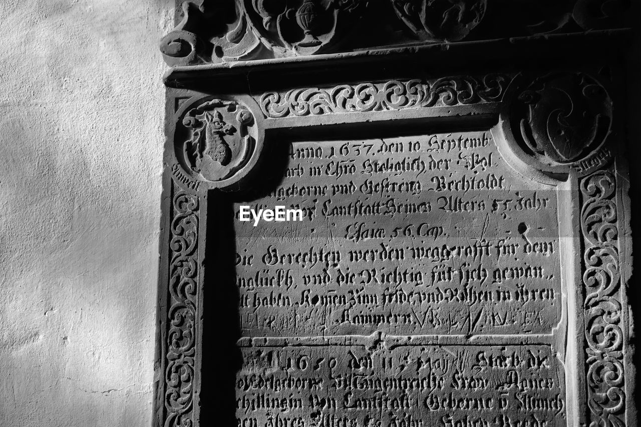 text, architecture, western script, communication, wall - building feature, no people, history, built structure, the past, day, building exterior, old, close-up, information, memorial, script, non-western script, low angle view, art and craft, craft, government, carving