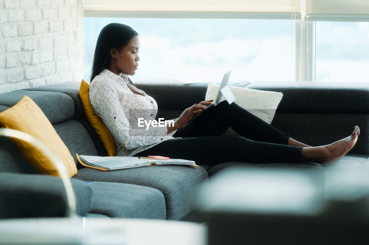 Full length of businesswoman using laptop sitting on sofa at home