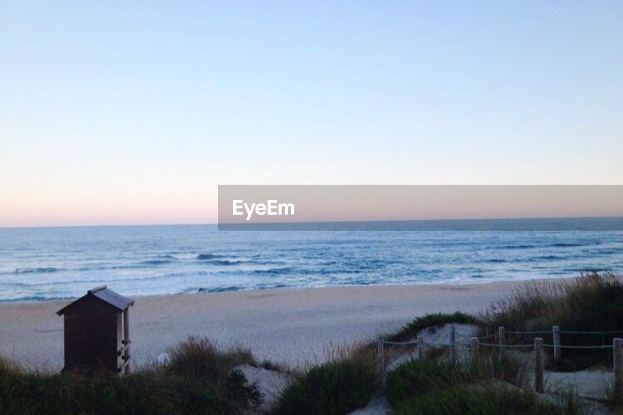 sea, horizon over water, beach, tranquil scene, scenics, tranquility, water, beauty in nature, clear sky, no people, sand, nature, wave, sky, built structure, sunset, outdoors, architecture, day, grass, marram grass, building exterior