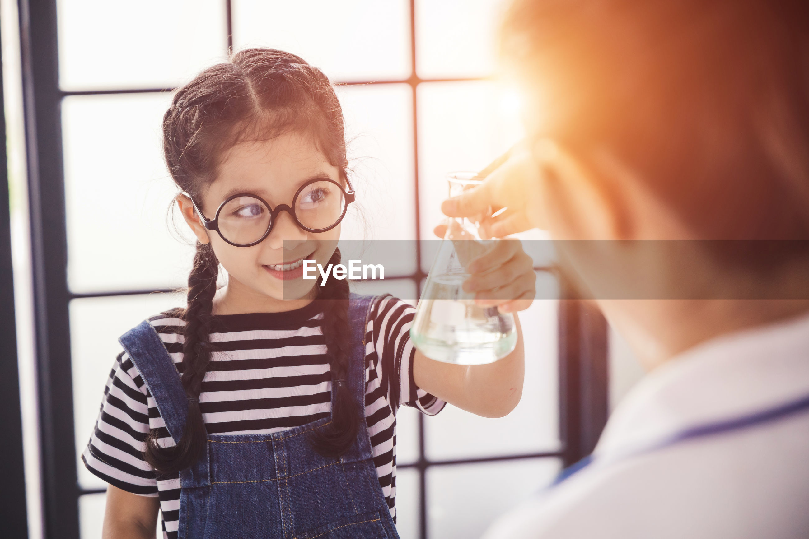 Smiling girl wearing glasses holding flask in laboratory