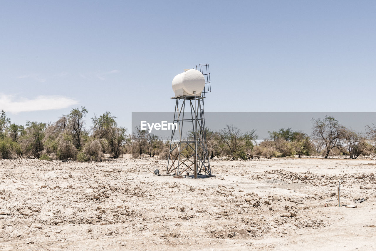 Water tower on land against sky during sunny day