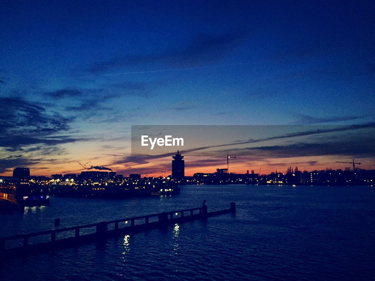 sunset, architecture, built structure, sky, building exterior, dusk, illuminated, river, city, cloud - sky, water, blue, outdoors, no people, night, skyscraper, cityscape, nature