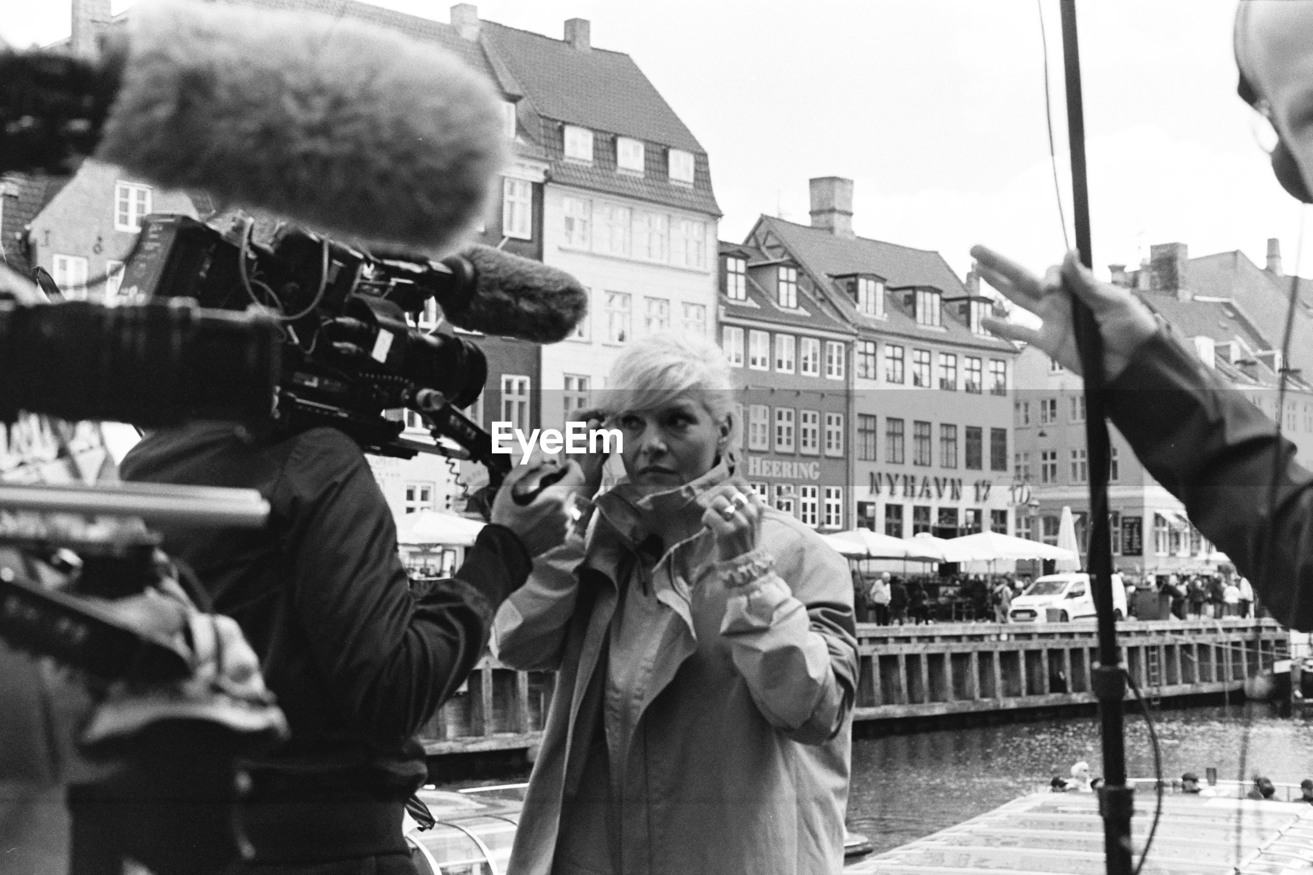 Woman with camera operator standing in city