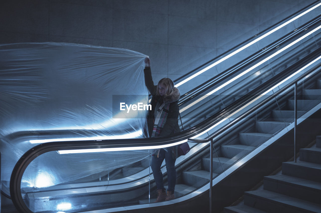 Young Woman Holding Plastic On Escalator