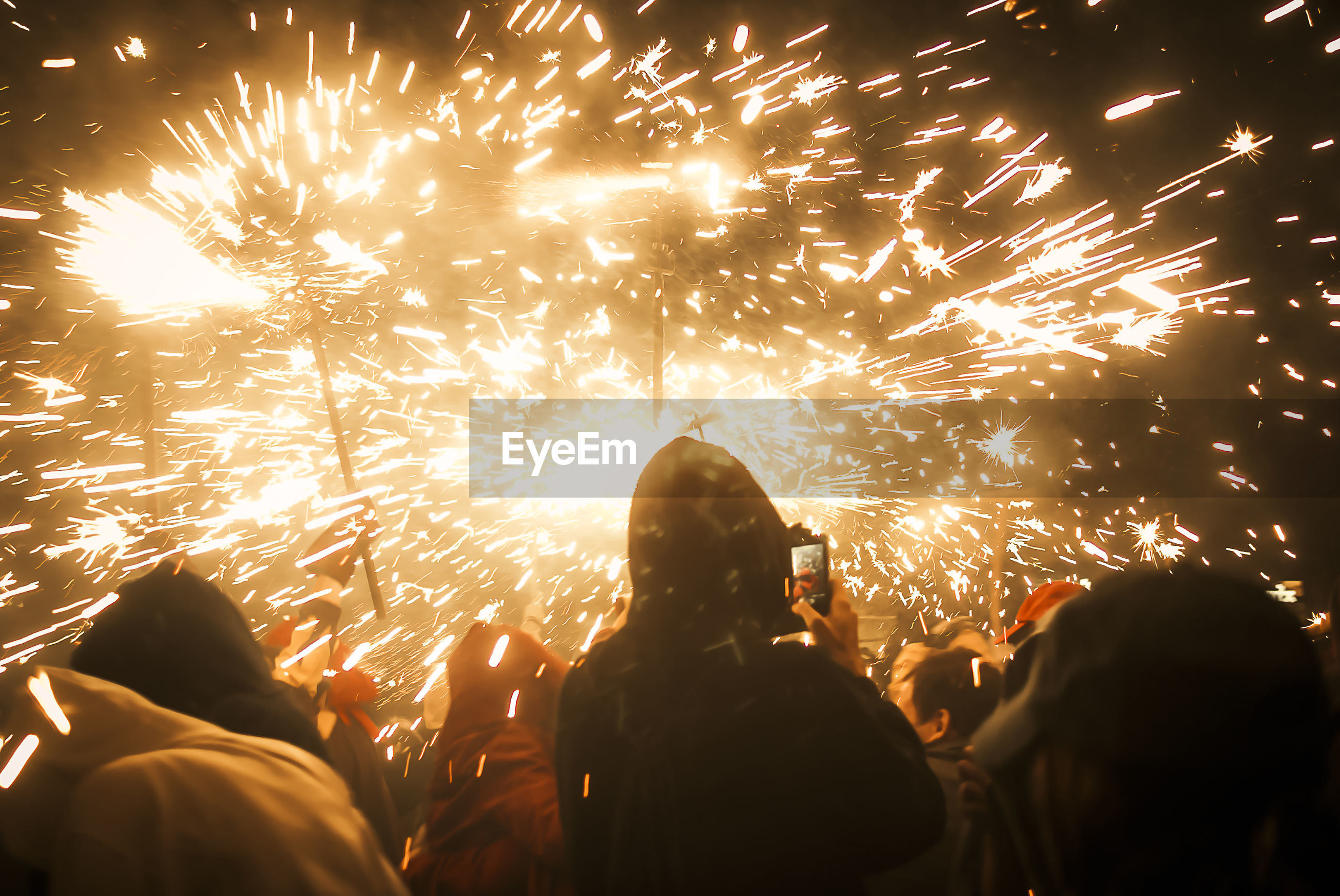 Rear view of people looking at fireworks display against sky at night