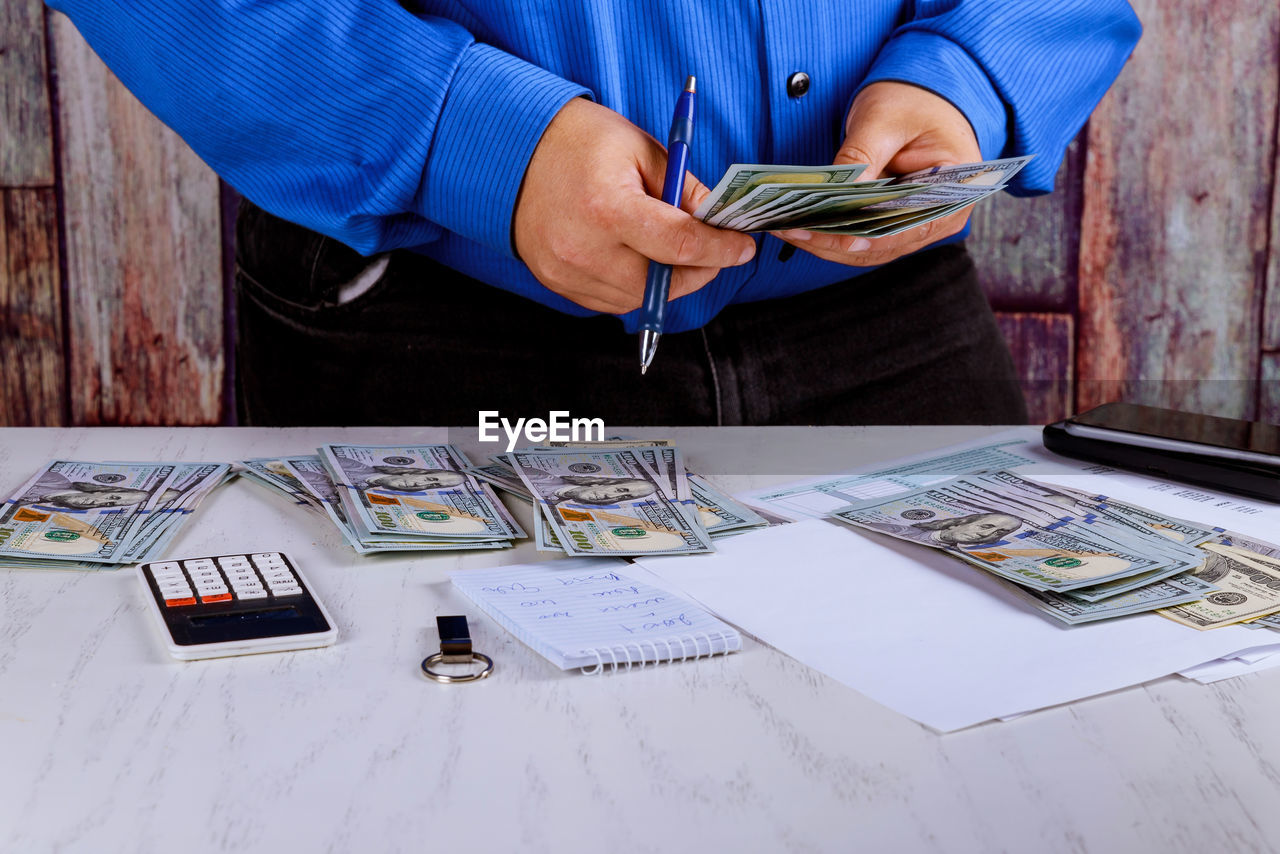 Midsection of businessman counting paper currency at desk in office