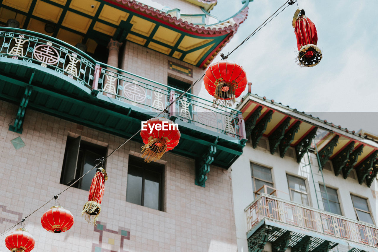 LOW ANGLE VIEW OF RED LANTERNS HANGING BY BUILDING