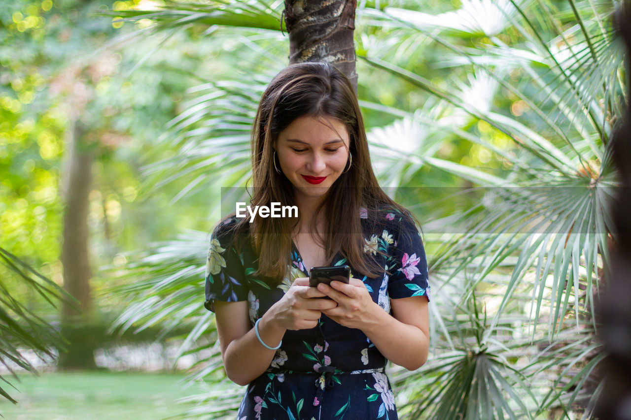 BEAUTIFUL YOUNG WOMAN USING PHONE WHILE STANDING BY TREE