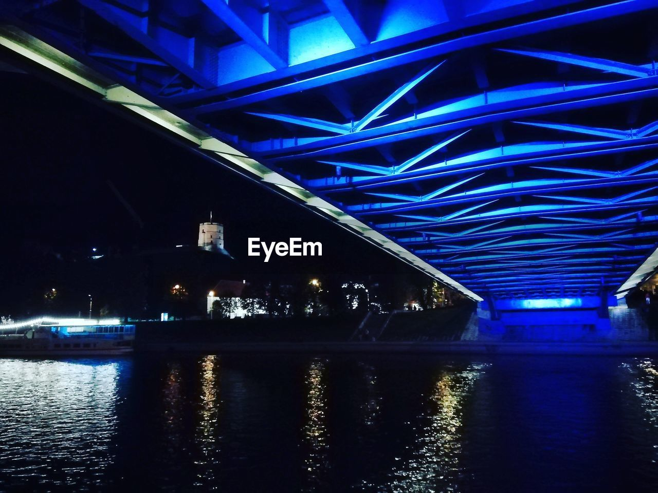 illuminated, night, architecture, reflection, built structure, water, waterfront, bridge, bridge - man made structure, river, lighting equipment, no people, connection, transportation, building exterior, nature, city, blue, glowing, light, ceiling, underneath