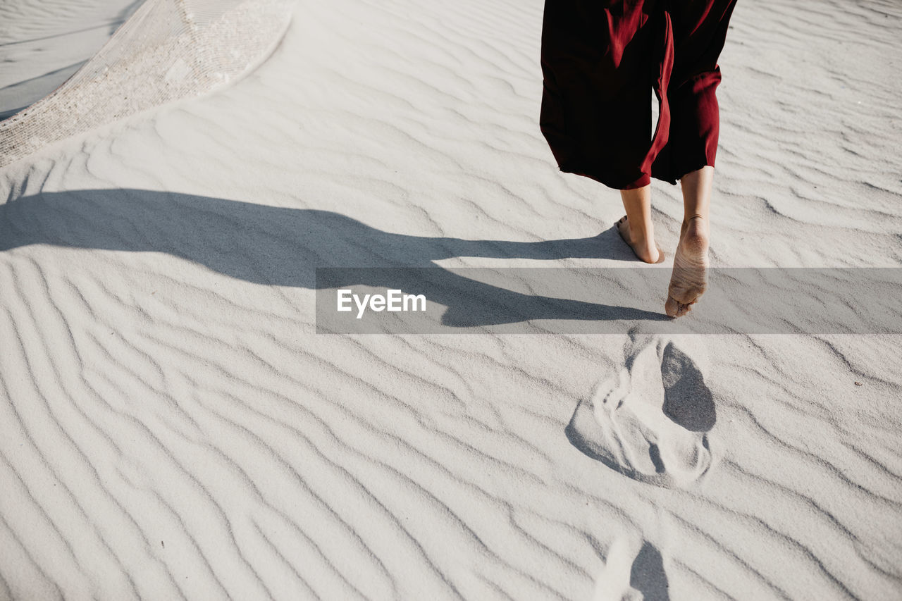 Low Section Of Woman Walking On Sand At Desert