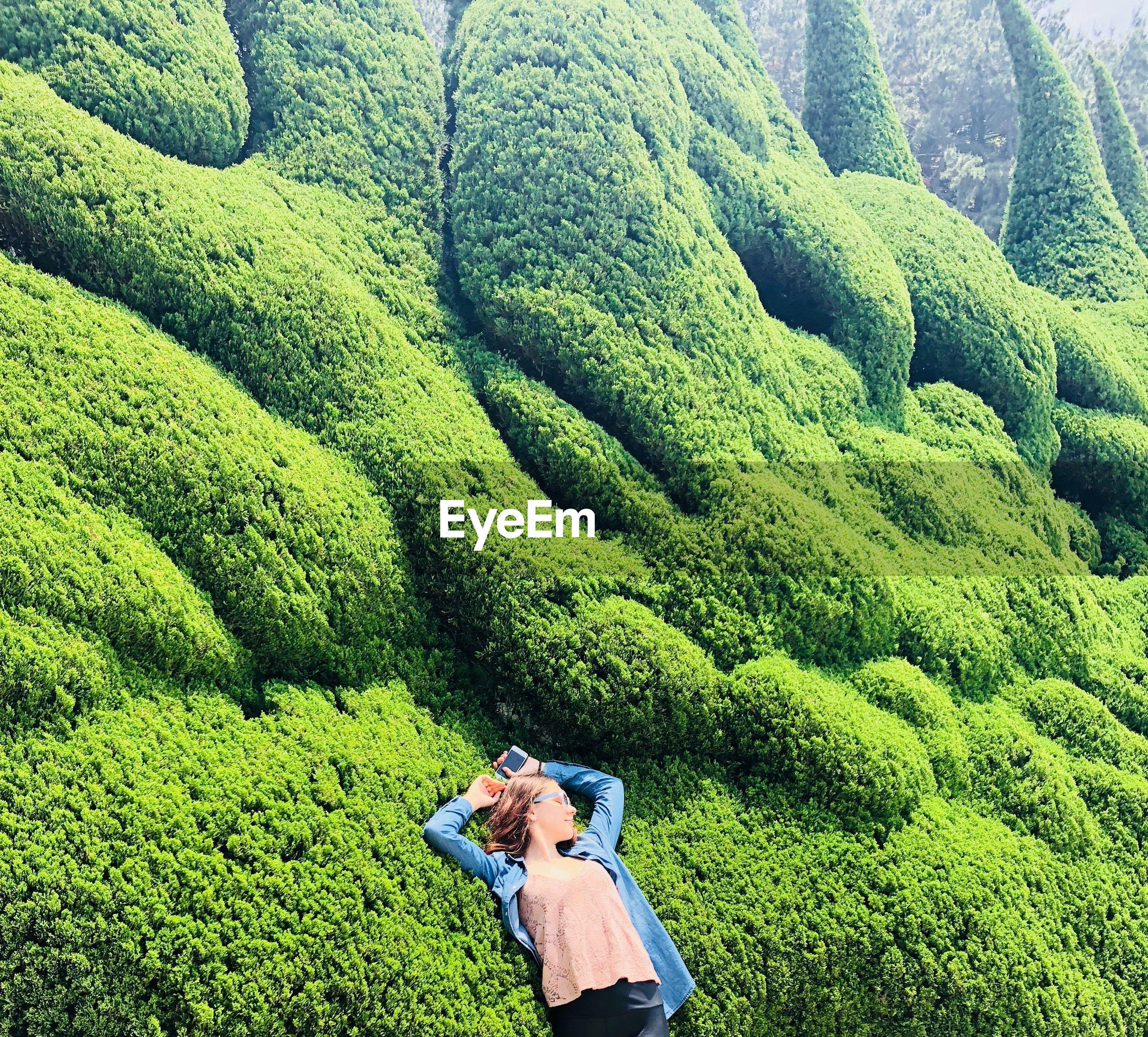 High angle view of woman lying on green mountain