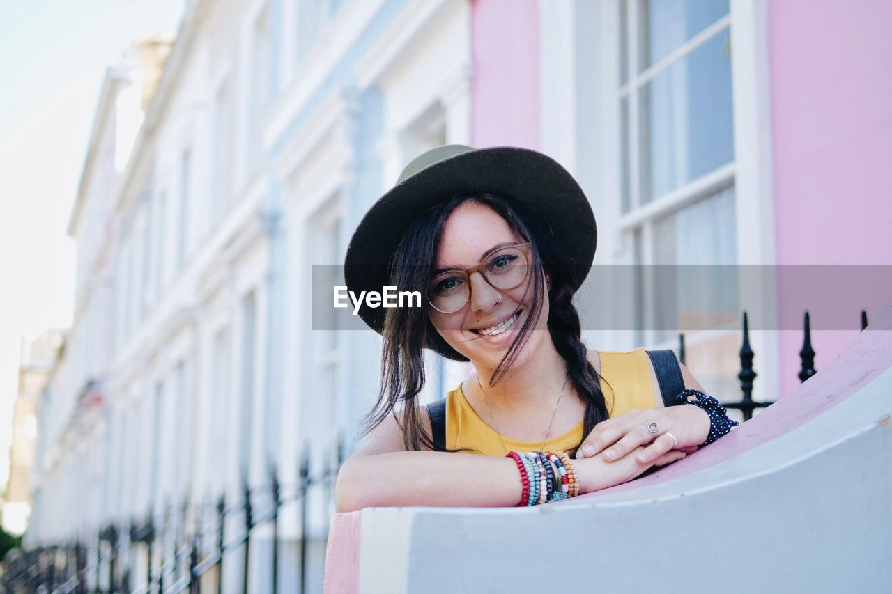 Portrait Of Smiling Woman Wearing Hat In City