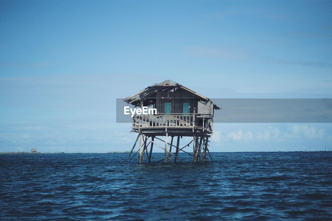 Abandoned Stilt House In Sea Against Sky