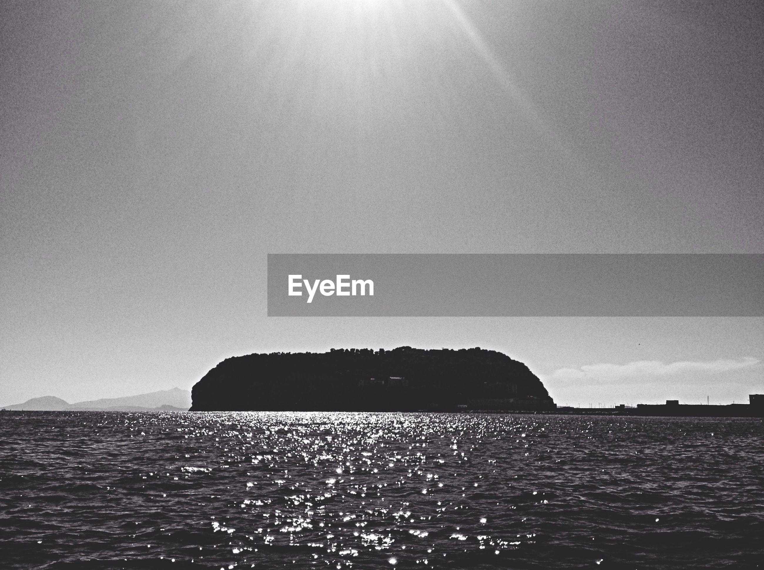 Silhouette mountain amidst sea against sky