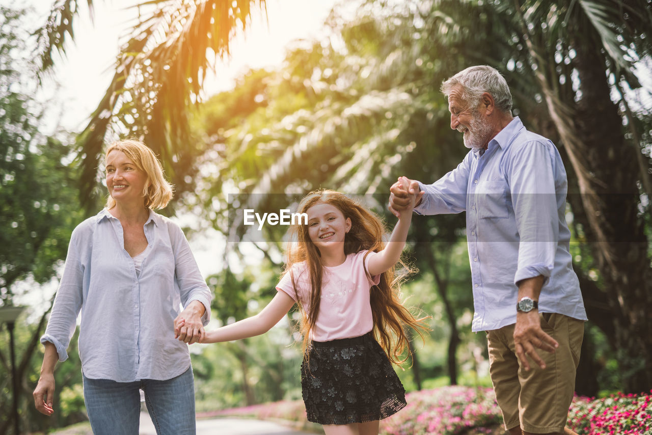 Portrait Of Happy Girl Holding Hands Of Grandparents While Standing On Road