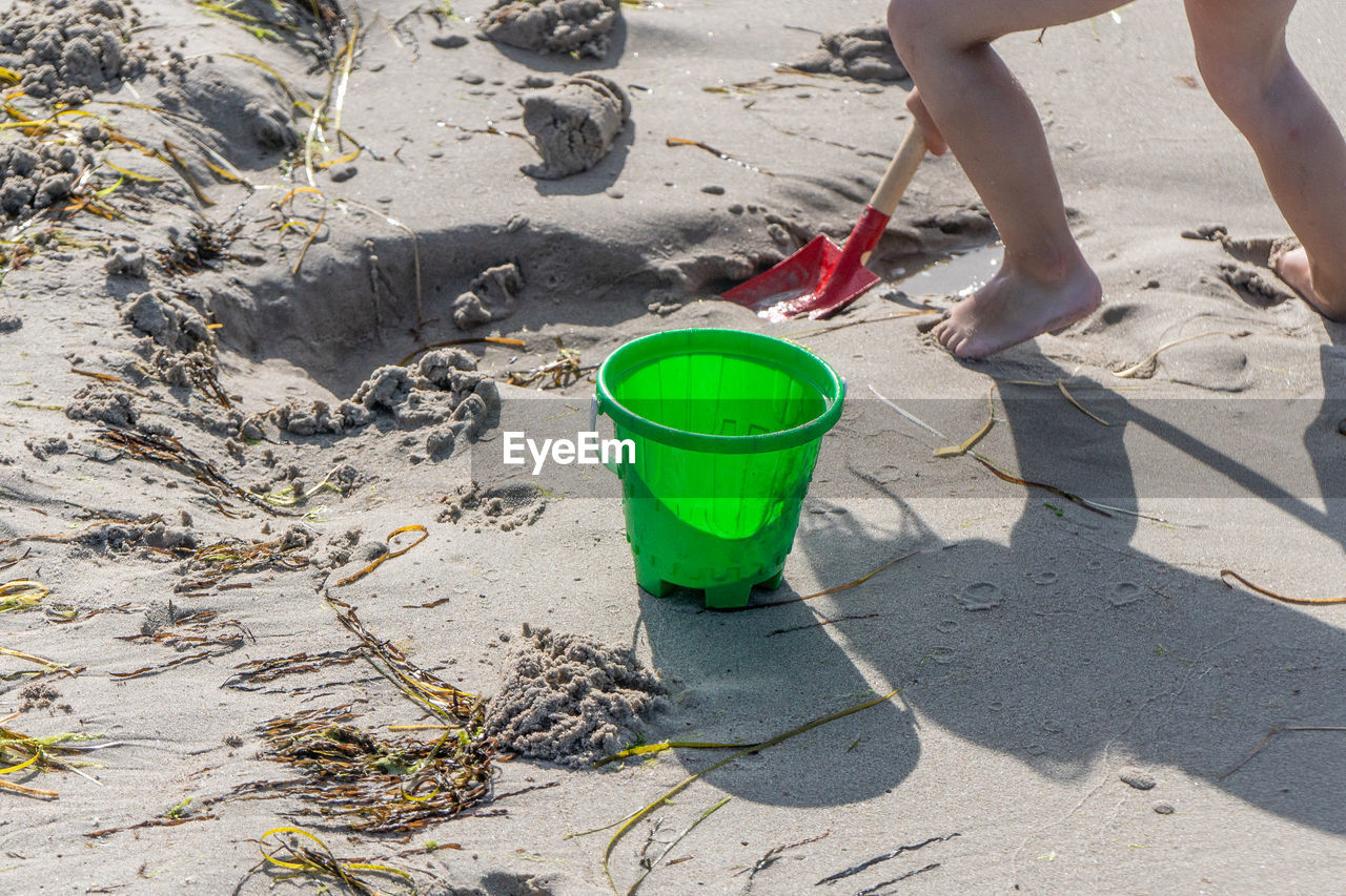 low section, drink, nature, day, refreshment, people, human leg, bucket, lifestyles, green color, beach, leisure activity, sand, land, human body part, real people, body part, standing, holding, outdoors, glass, human foot