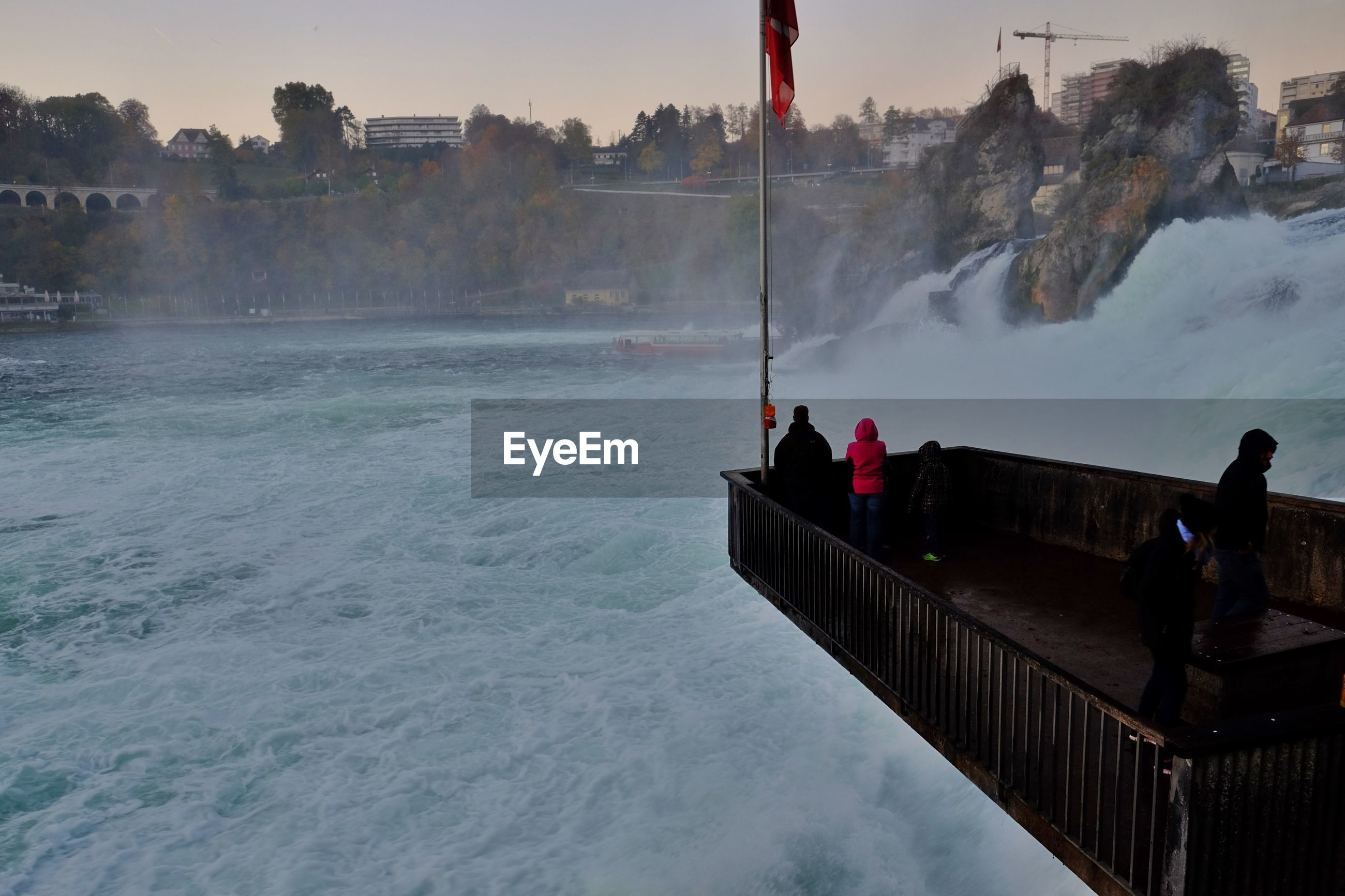 People looking at rhine falls from observation point