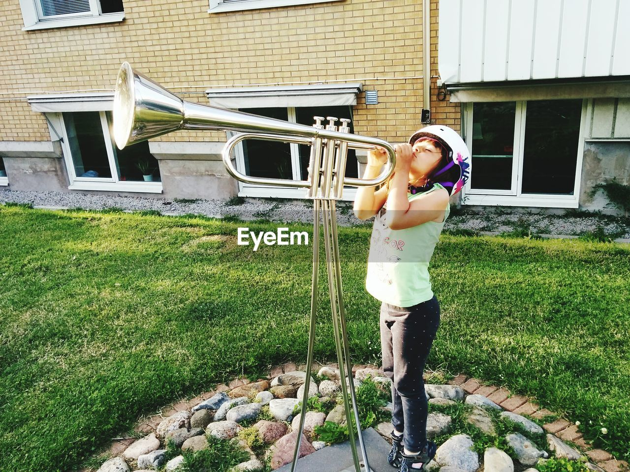 Girl Playing Trumpet Outside Building