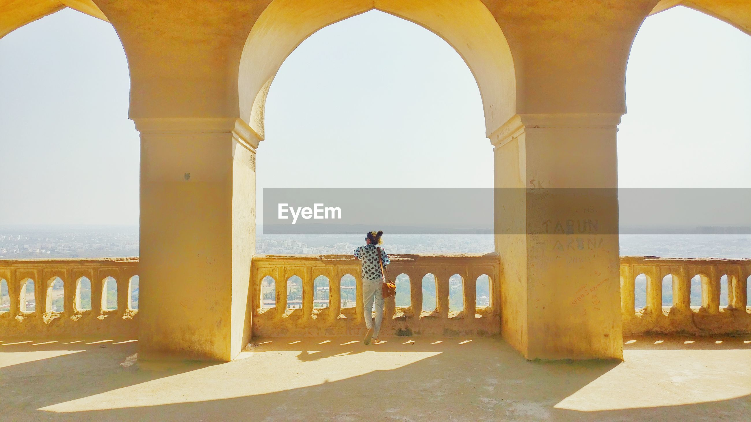 Rear view of woman standing at historic building during sunny day