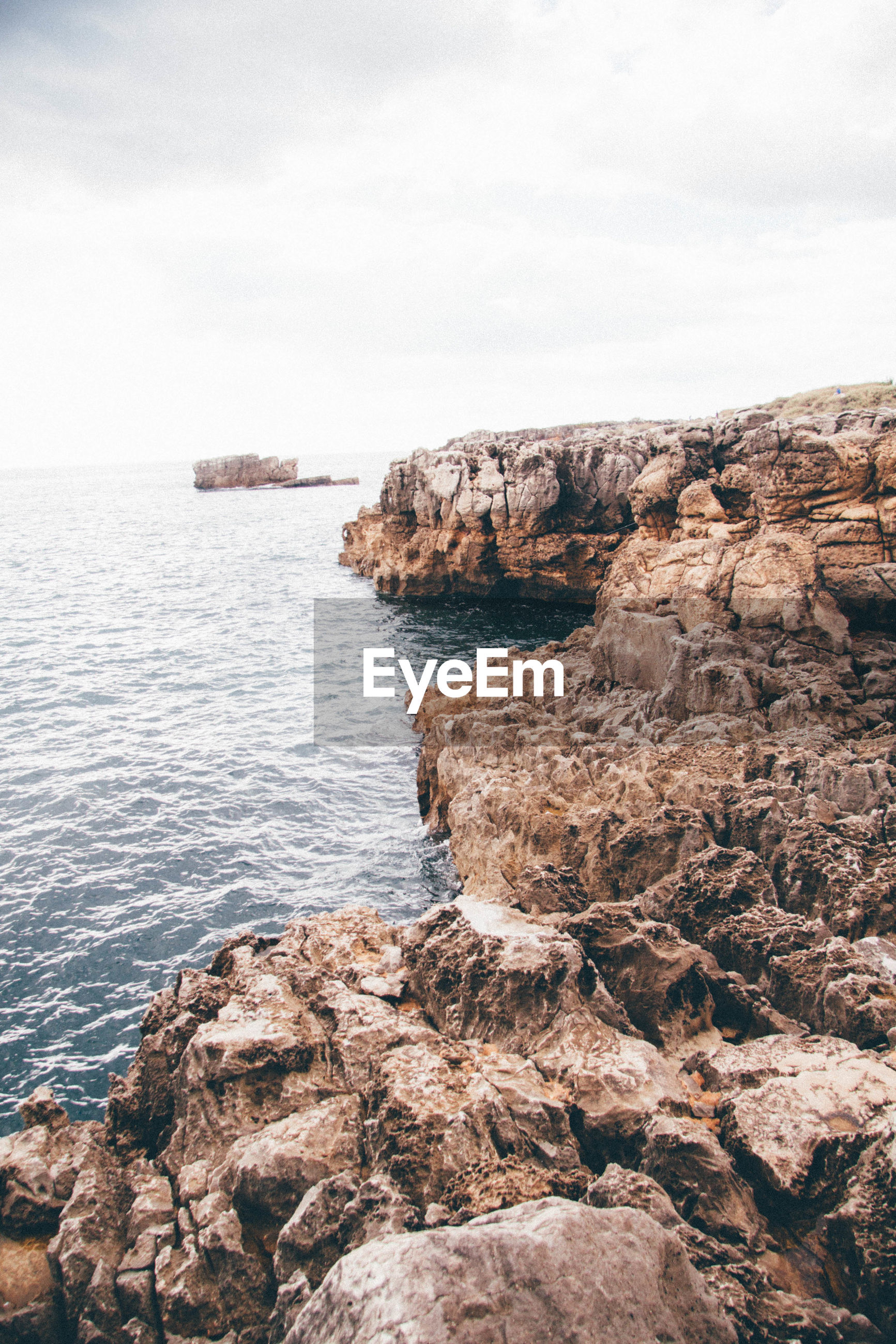 Rock formations by sea against cloudy sky