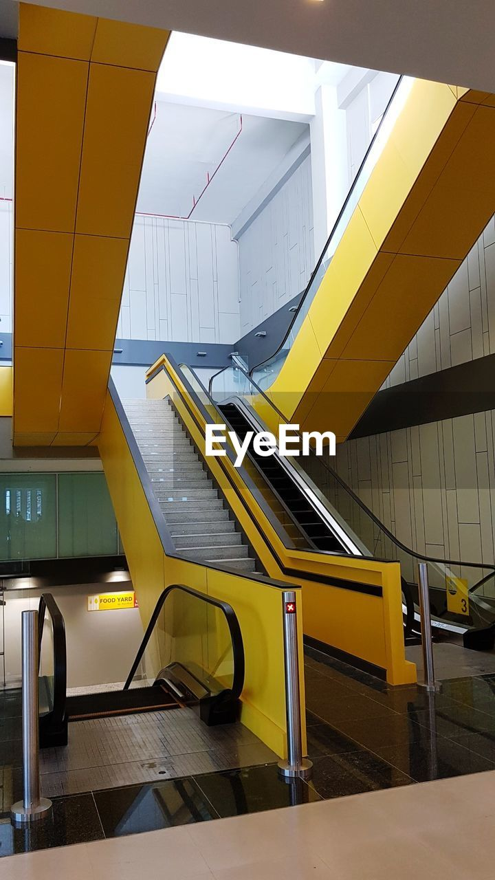yellow, architecture, escalator, staircase, built structure, indoors, seat, no people, steps and staircases, transportation, railing, modern, glass - material, building, absence, empty, subway station, connection, mode of transportation, travel
