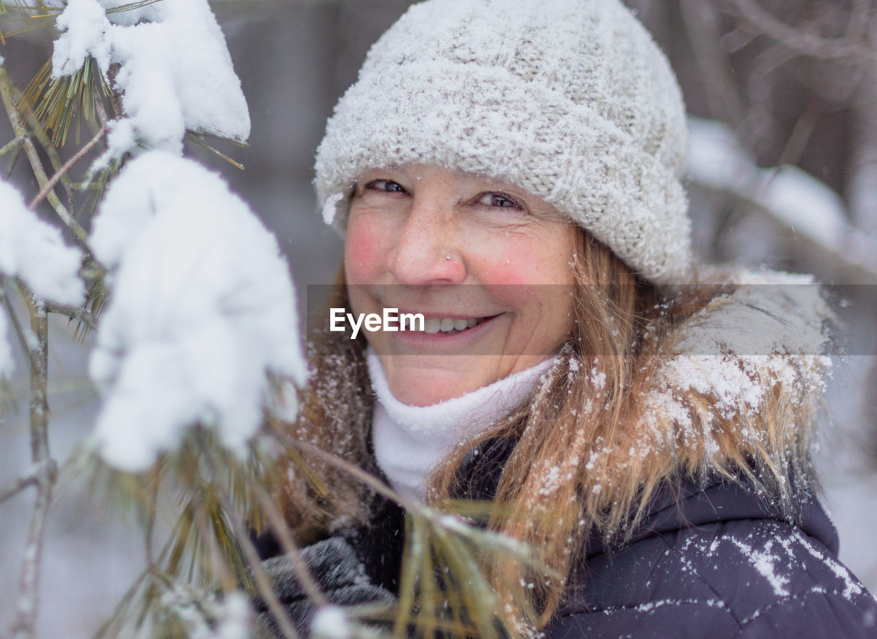 Portrait of smiling mature woman standing by plant during winter in forest