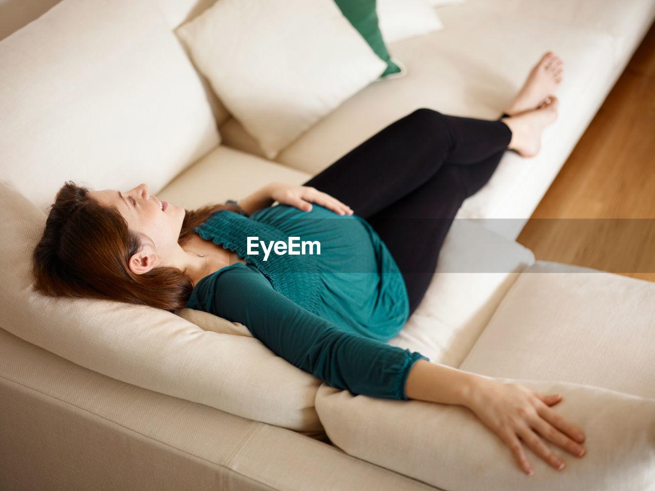 HIGH ANGLE VIEW OF WOMAN LYING DOWN ON SOFA