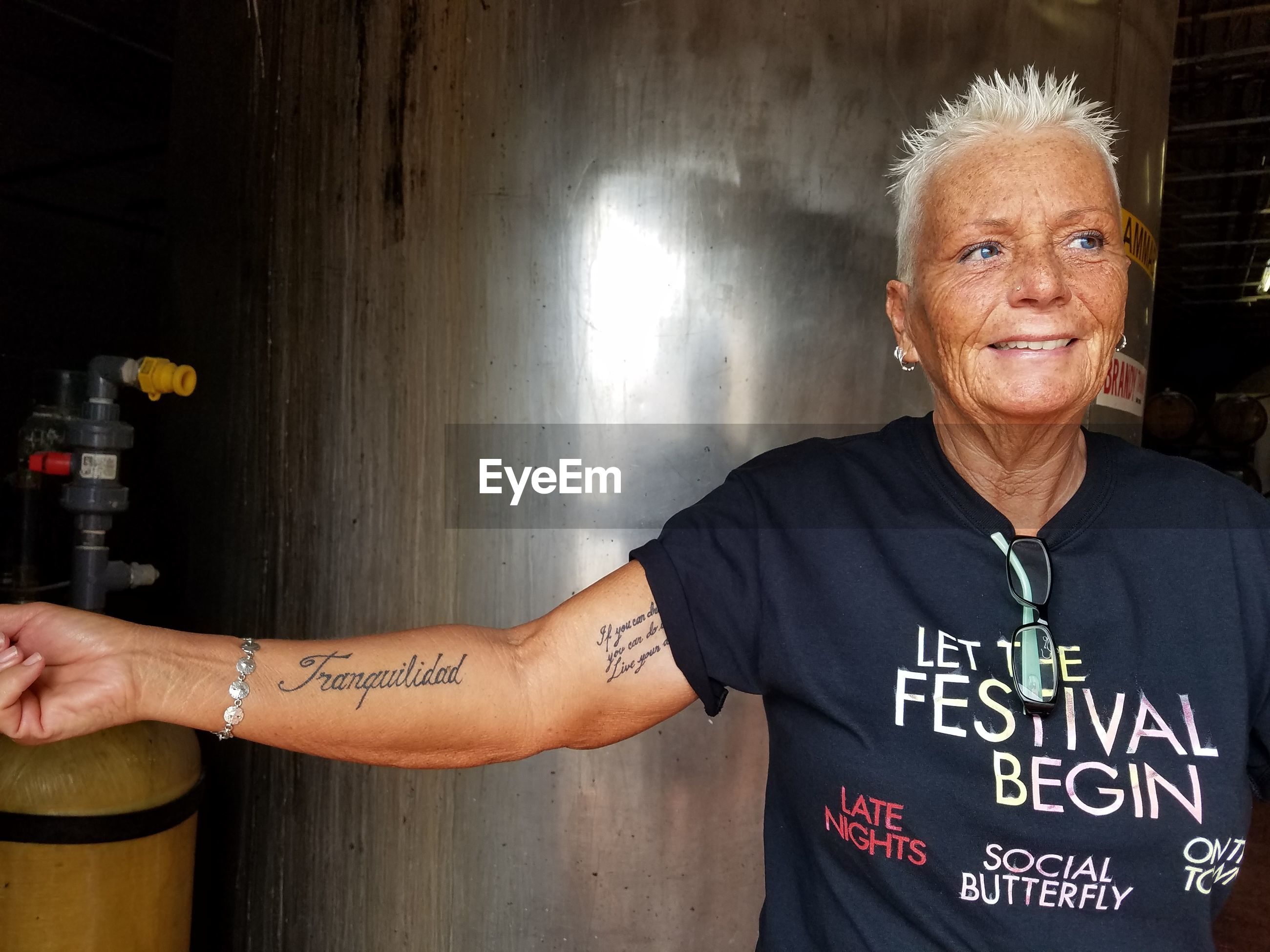 Senior woman with tattoo standing against metal container