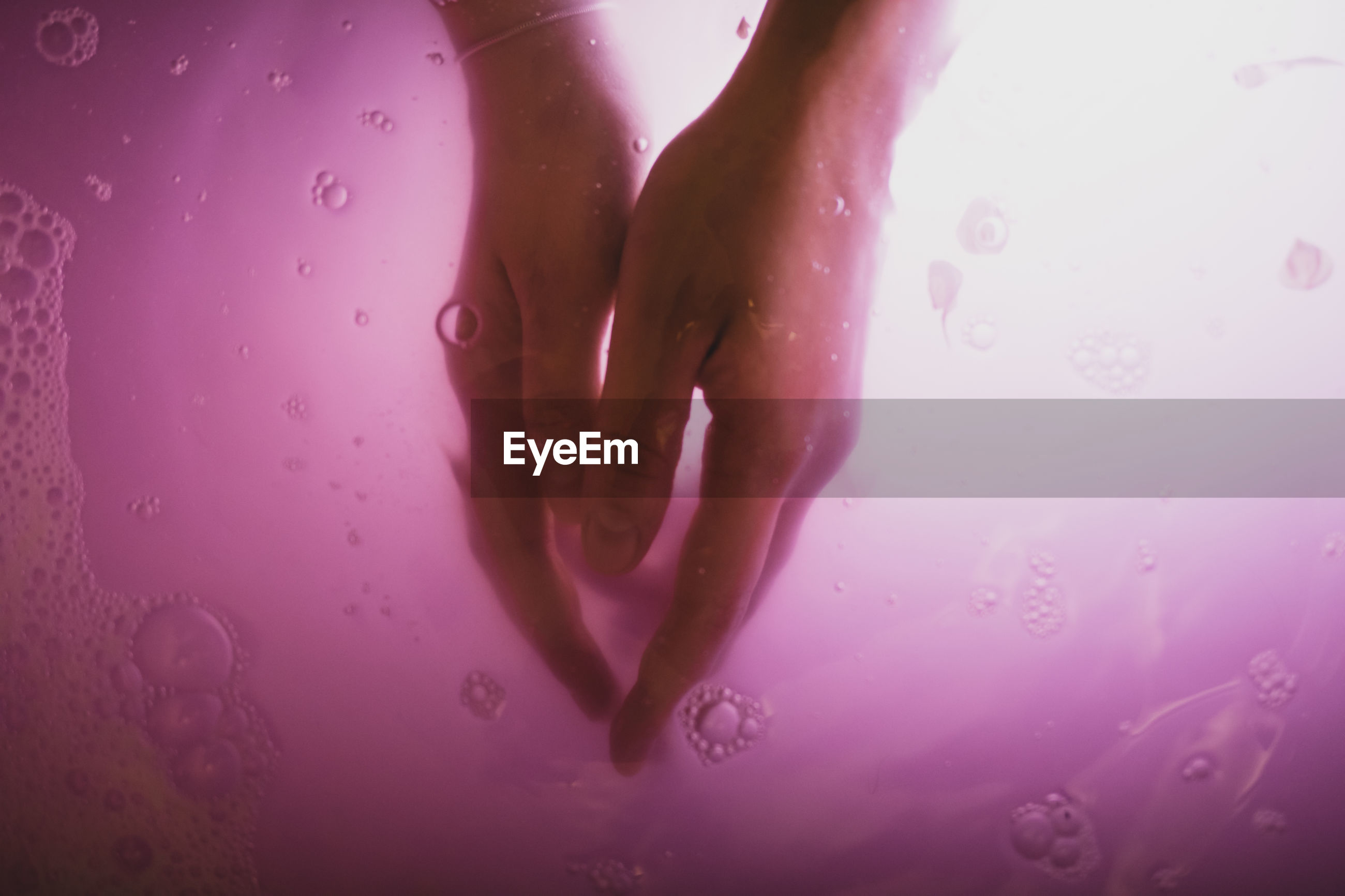Cropped hands of young woman in pink water