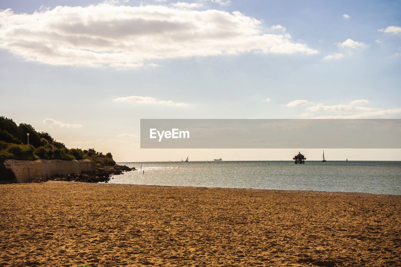 sea, water, sky, cloud - sky, beach, nature, beauty in nature, tranquility, scenics, sand, outdoors, no people, horizon over water, day, tree