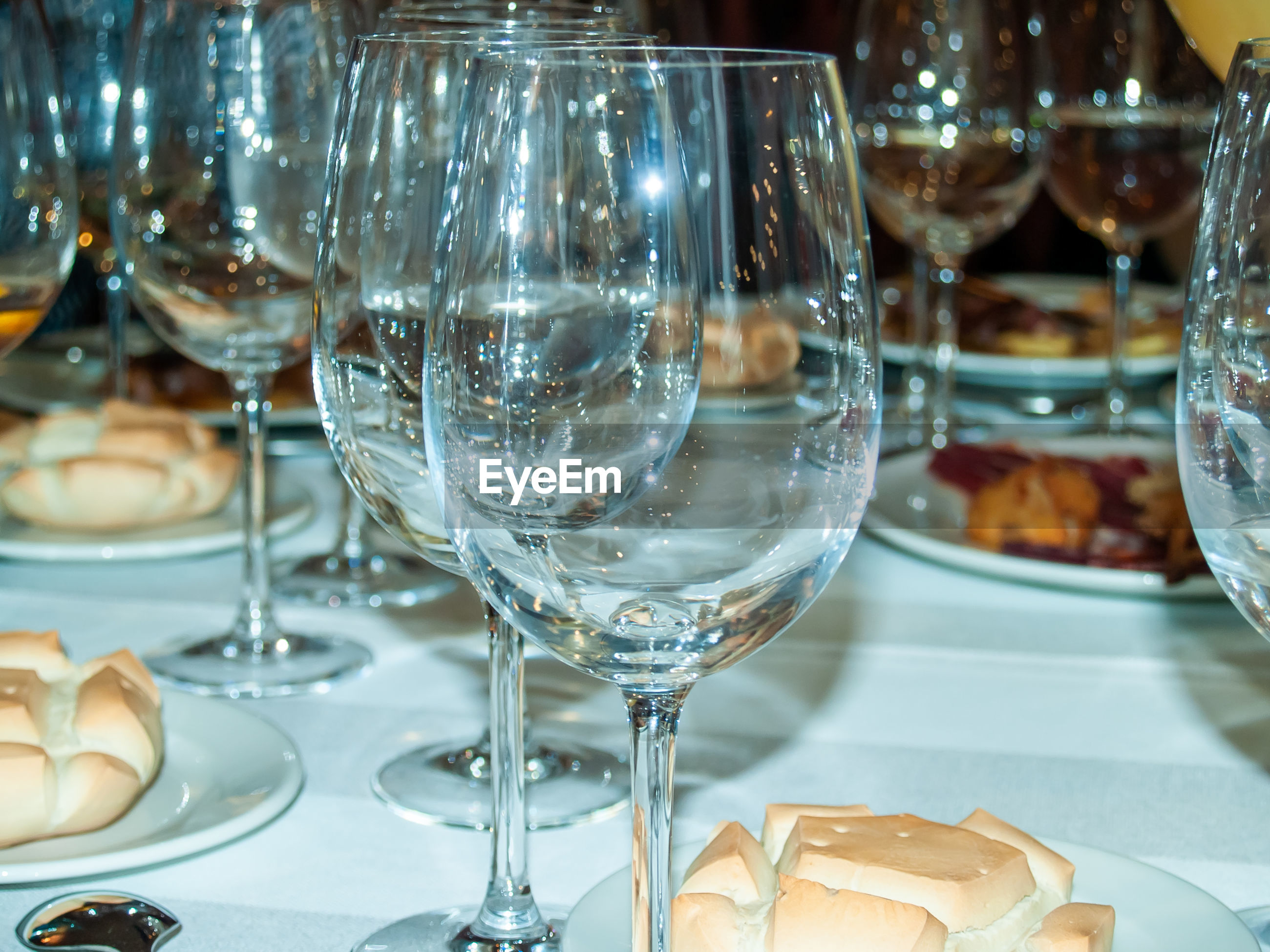CLOSE-UP OF WINE GLASSES ON GLASS TABLE