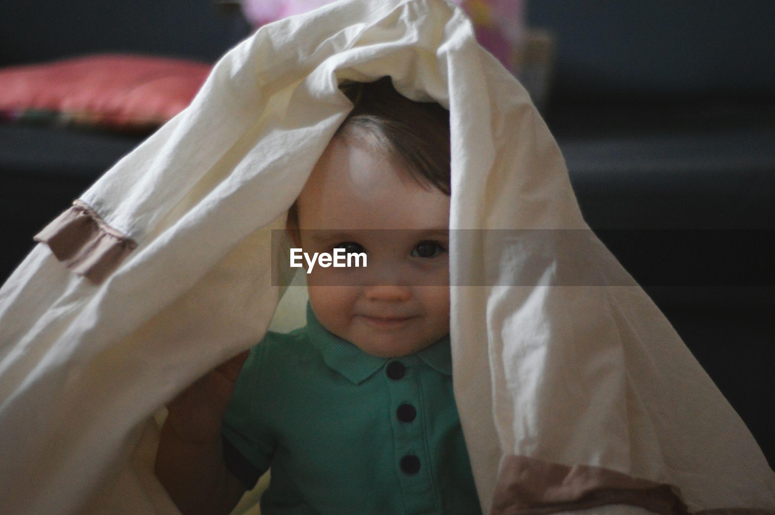 Portrait of cute baby girl under cloth