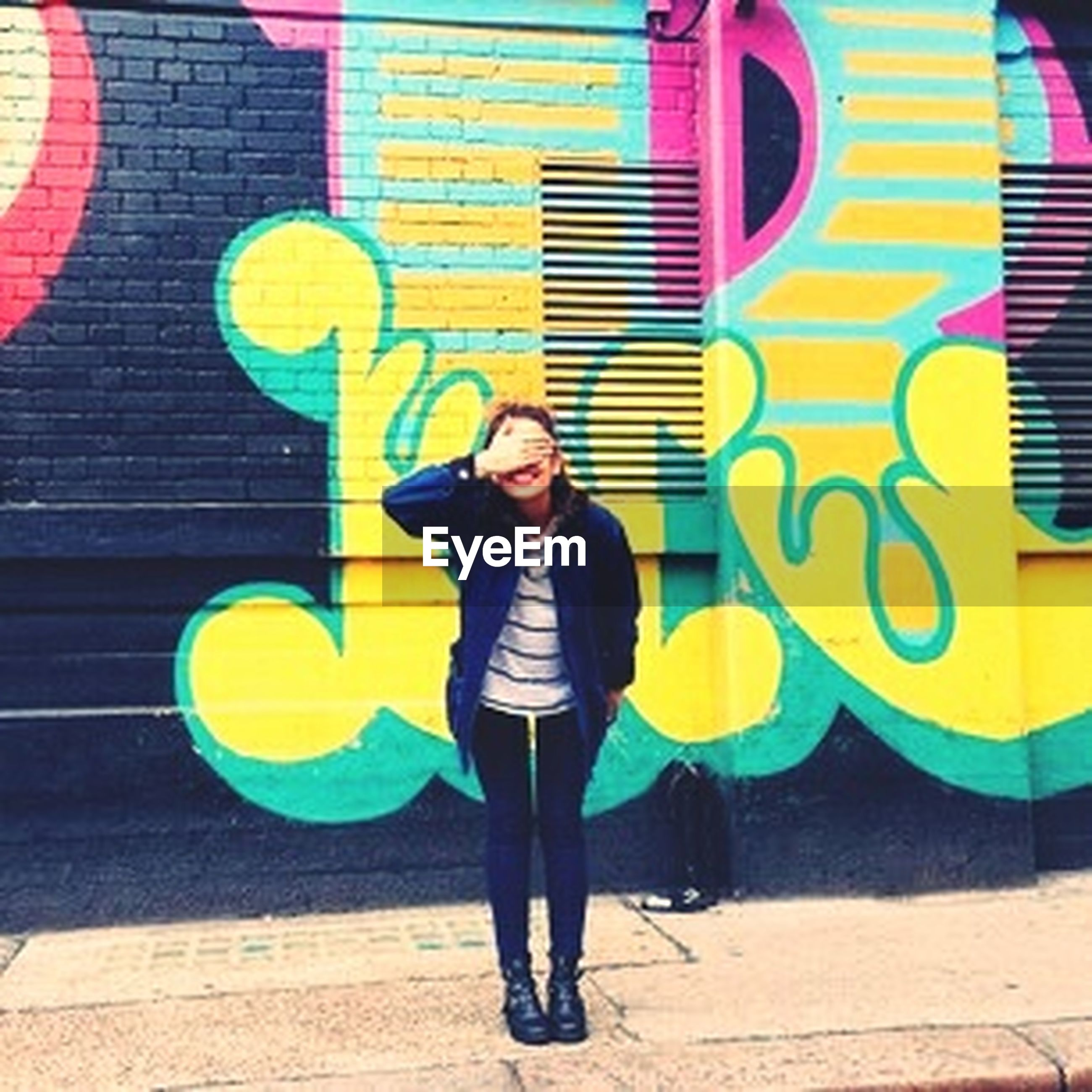 lifestyles, young adult, casual clothing, front view, full length, leisure activity, standing, portrait, person, looking at camera, young women, building exterior, built structure, sunglasses, architecture, happiness, smiling, graffiti