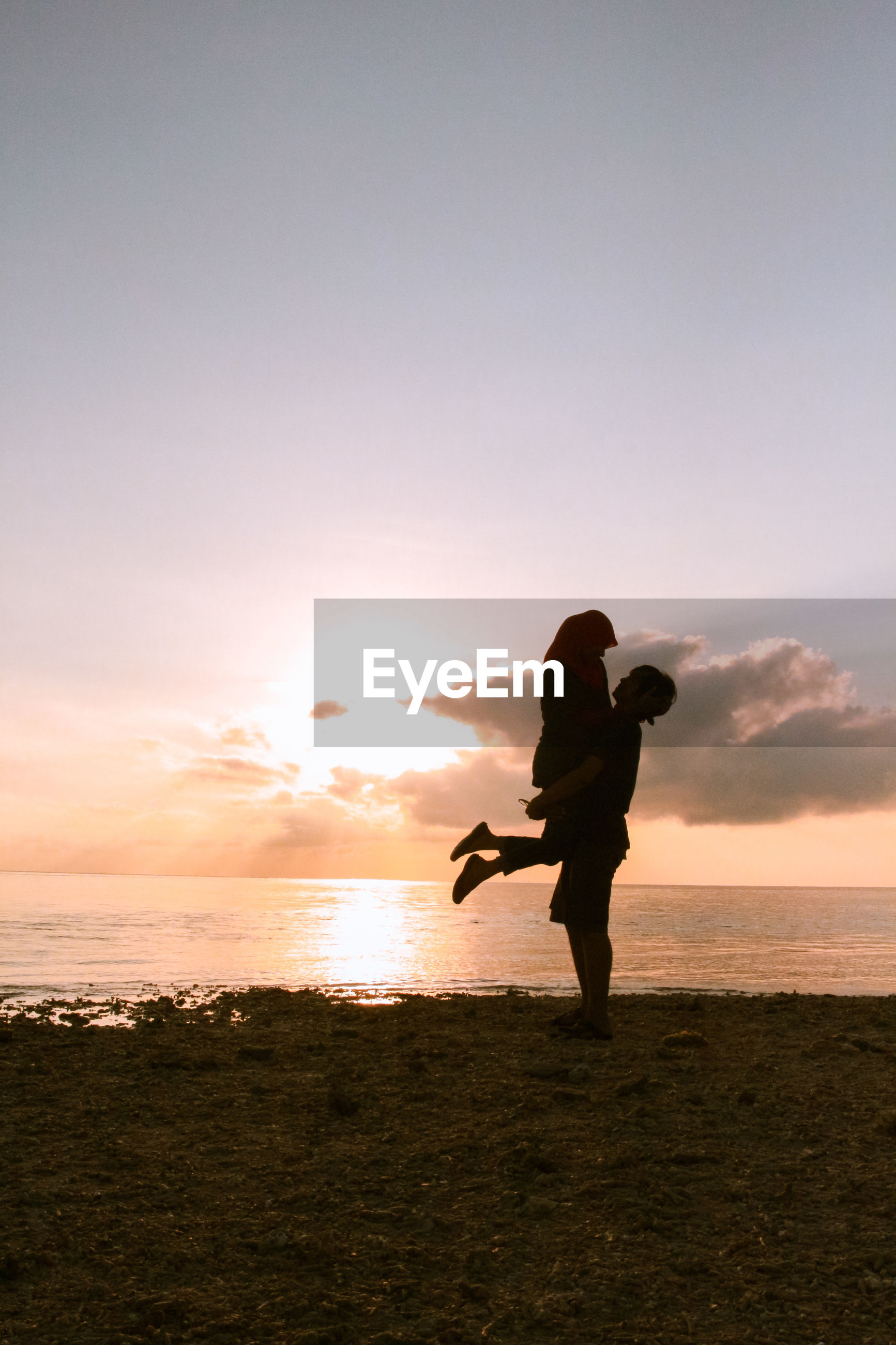 Silhouette of man carrying woman while standing at beach against sky during sunset
