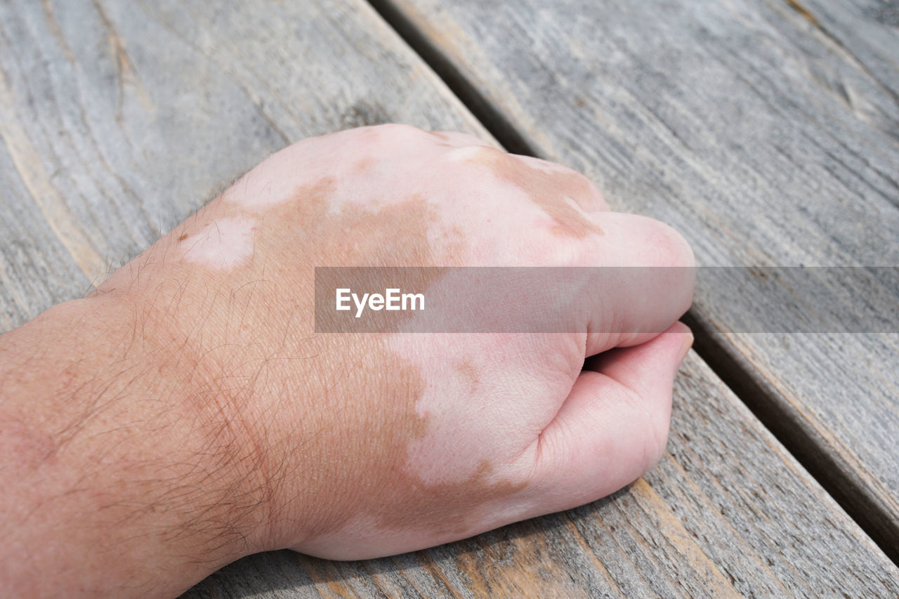Cropped Hand Of Man On Wooden Table